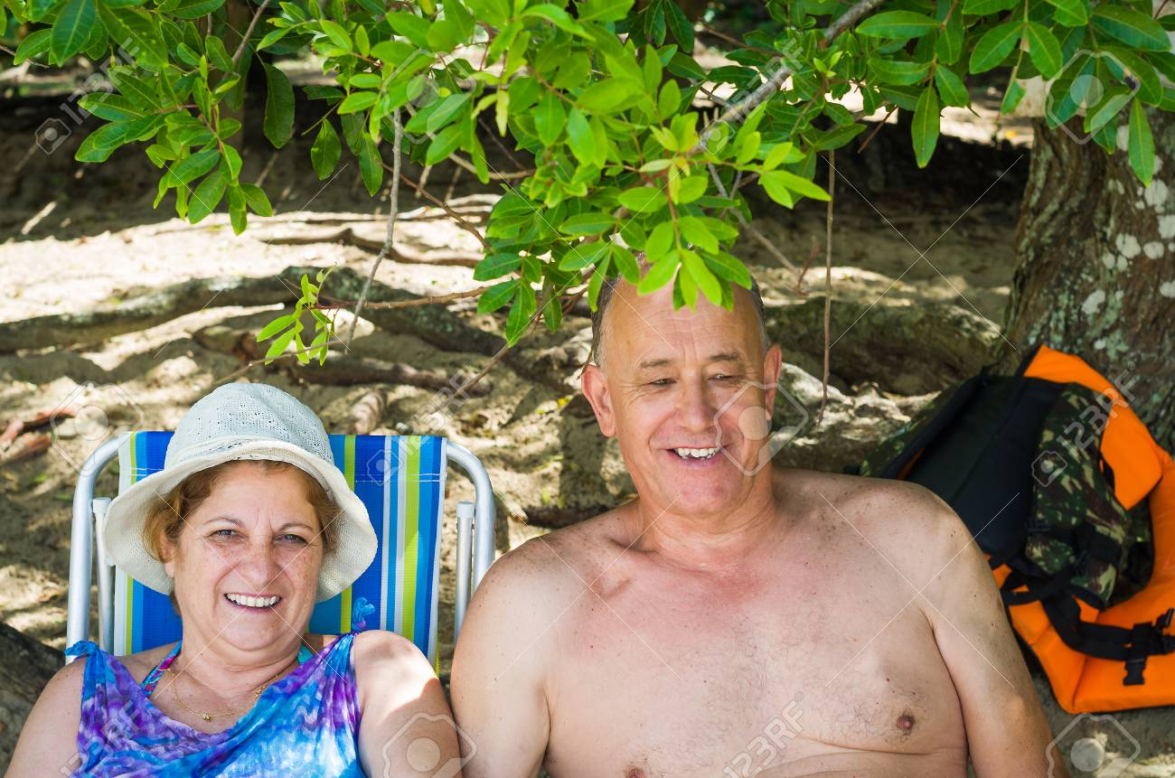 Old couple laughing on the beach, sitting, love. - 97418062