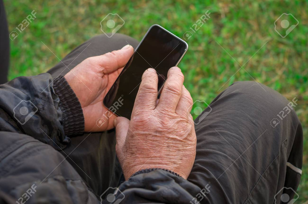 Close up of a wrinkled finger touching the smartphone, old man uses technology. Internet. - 98491849