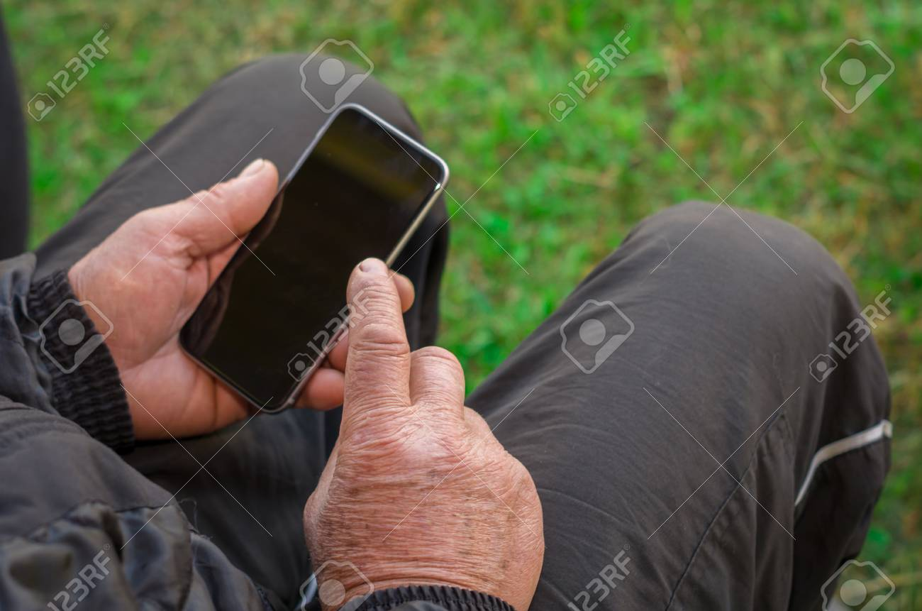 Close up of a wrinkled finger touching the smartphone, old man uses technology. Internet. - 98492082