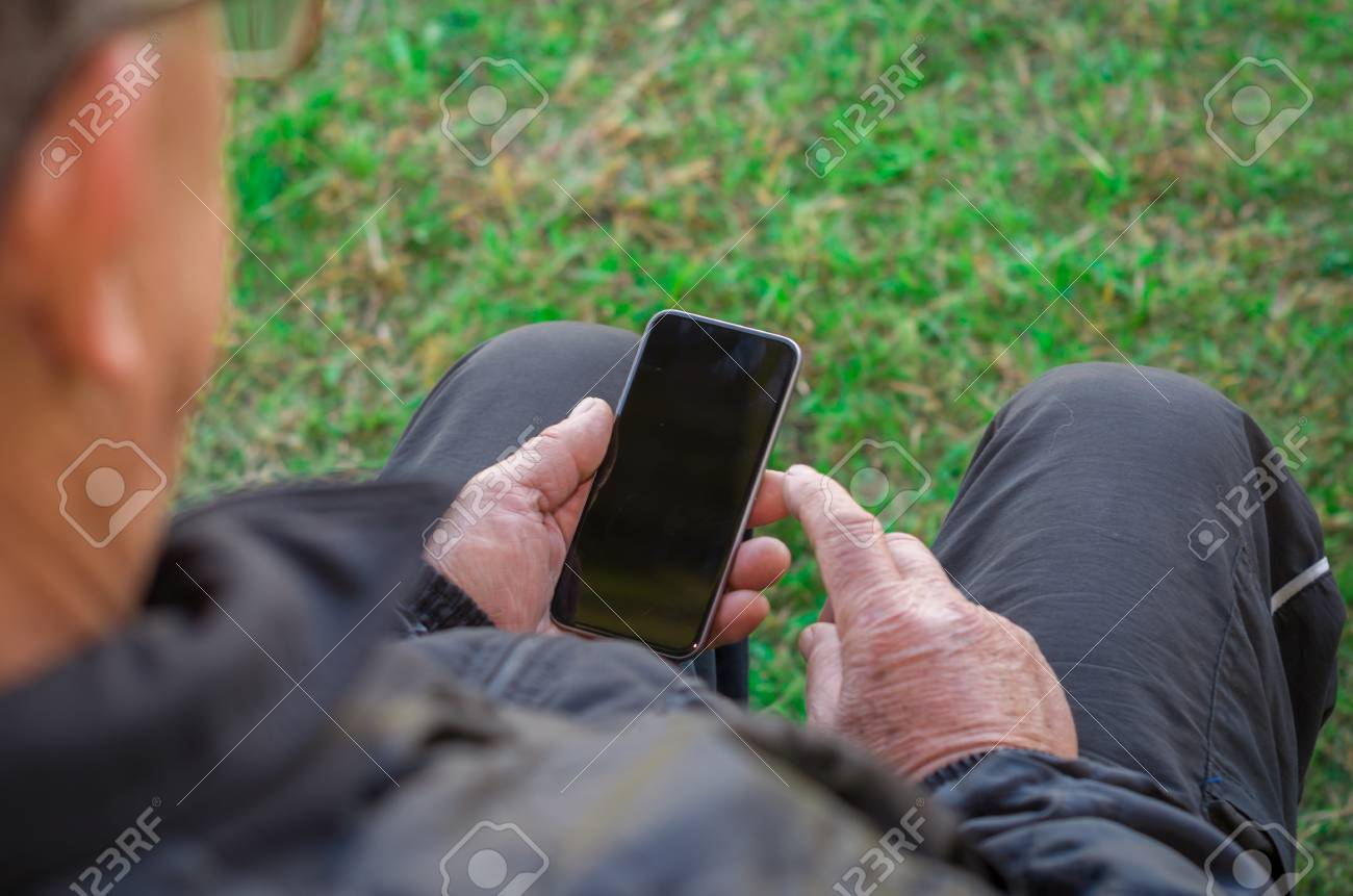 Close up of a man's wrinkled finger touching a cell phone - 98180864
