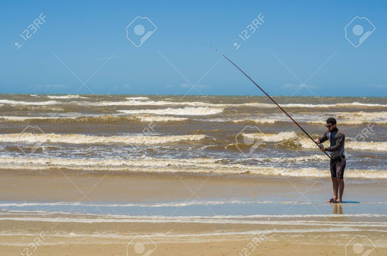 Young man fishing on beach, sport fishing. - 98185624