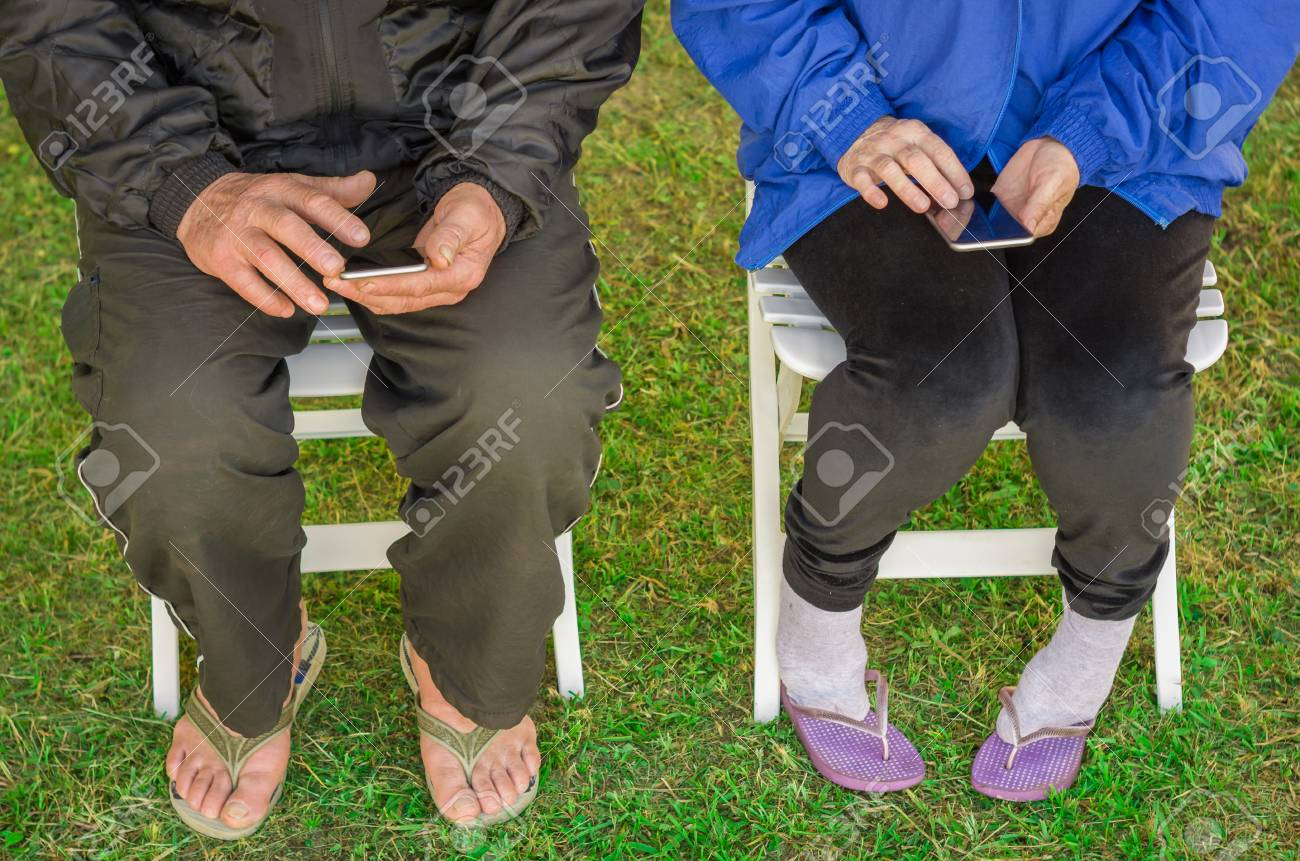 Close-up of senior couple sitting, using smartphone, cellphone, technology. - 98191502