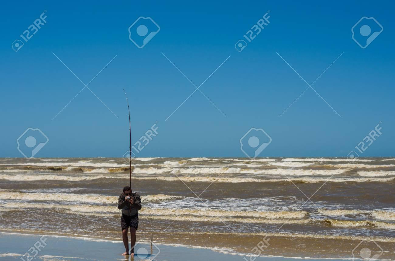 Young man fishing on beach, sport fishing. - 98185633