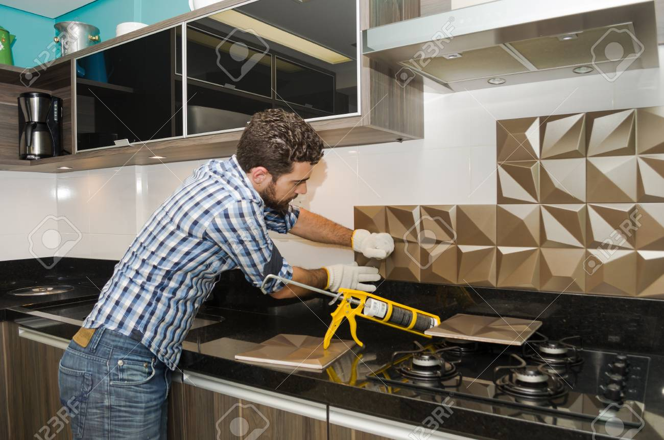 Man renovating, renovating the kitchen, installing tile on the..