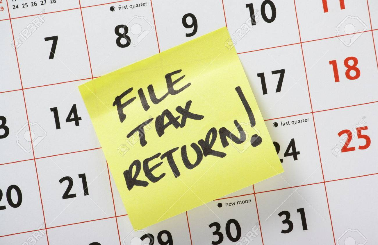 Hand Written Reminder To File Tax Return On A Yellow Post It Note Stuck To A