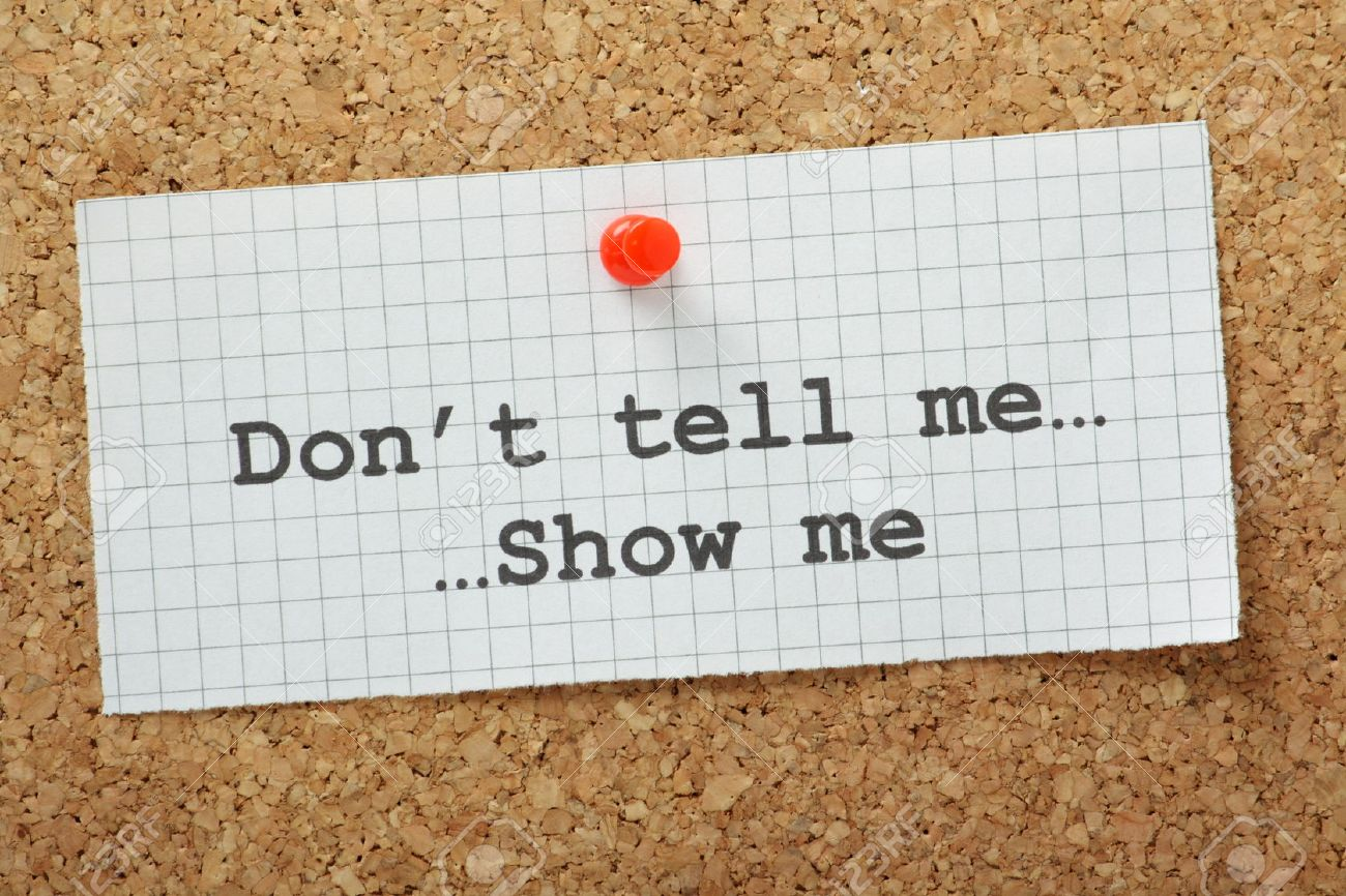 stock photo the phrase don t tell me show me typed on a piece of graph paper and pinned to a cork notice board often used in business but more so