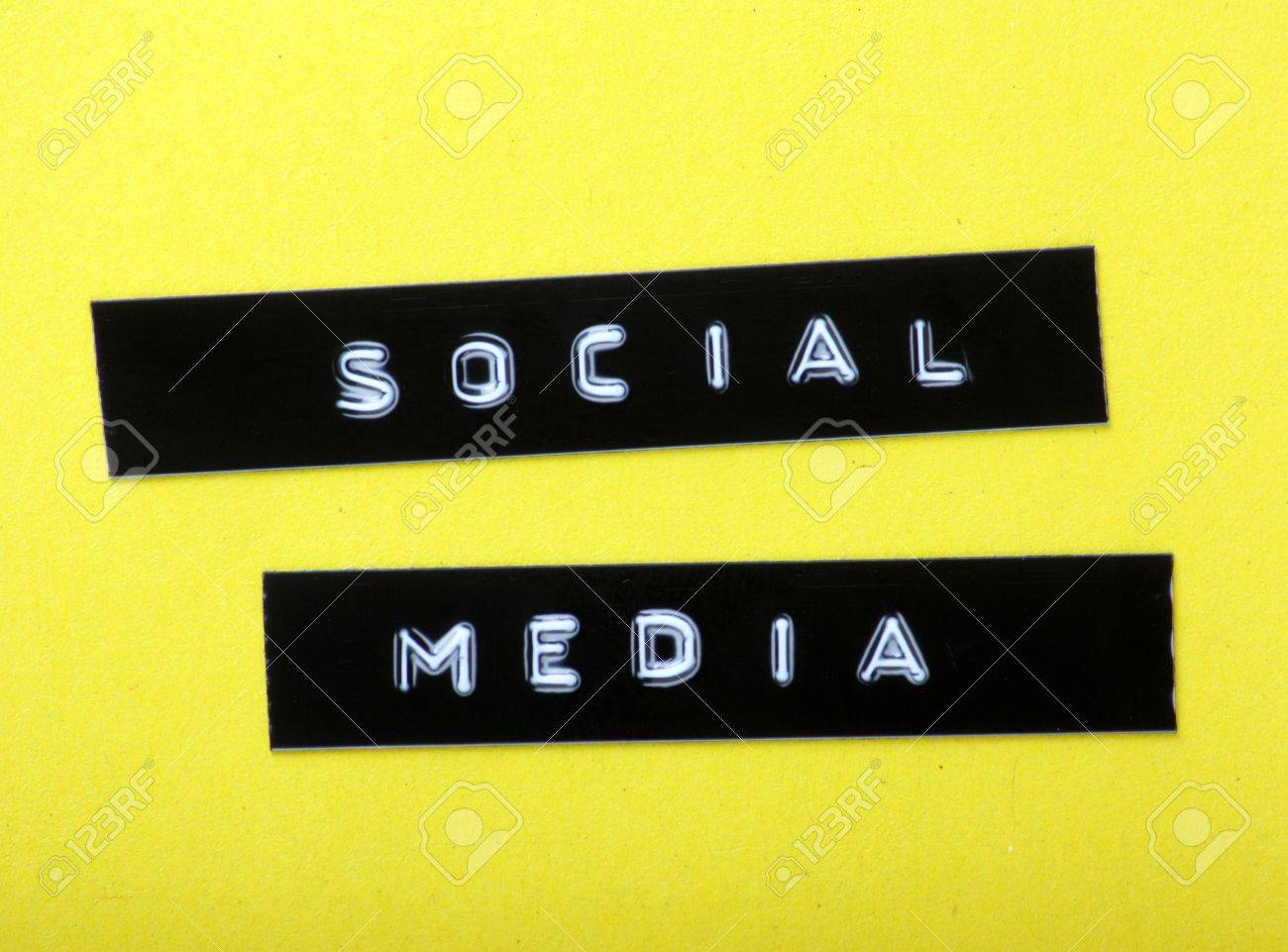 the words social media made into labels an embossed letter stock photo the words social media made into labels an embossed letter label maker and fixed to a yellow paper background