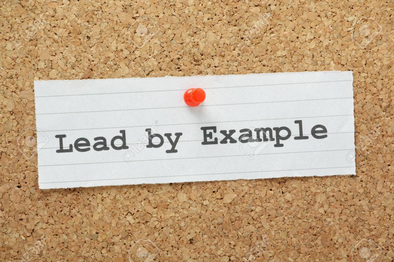 the phrase lead by example typed on a paper note and pinned to