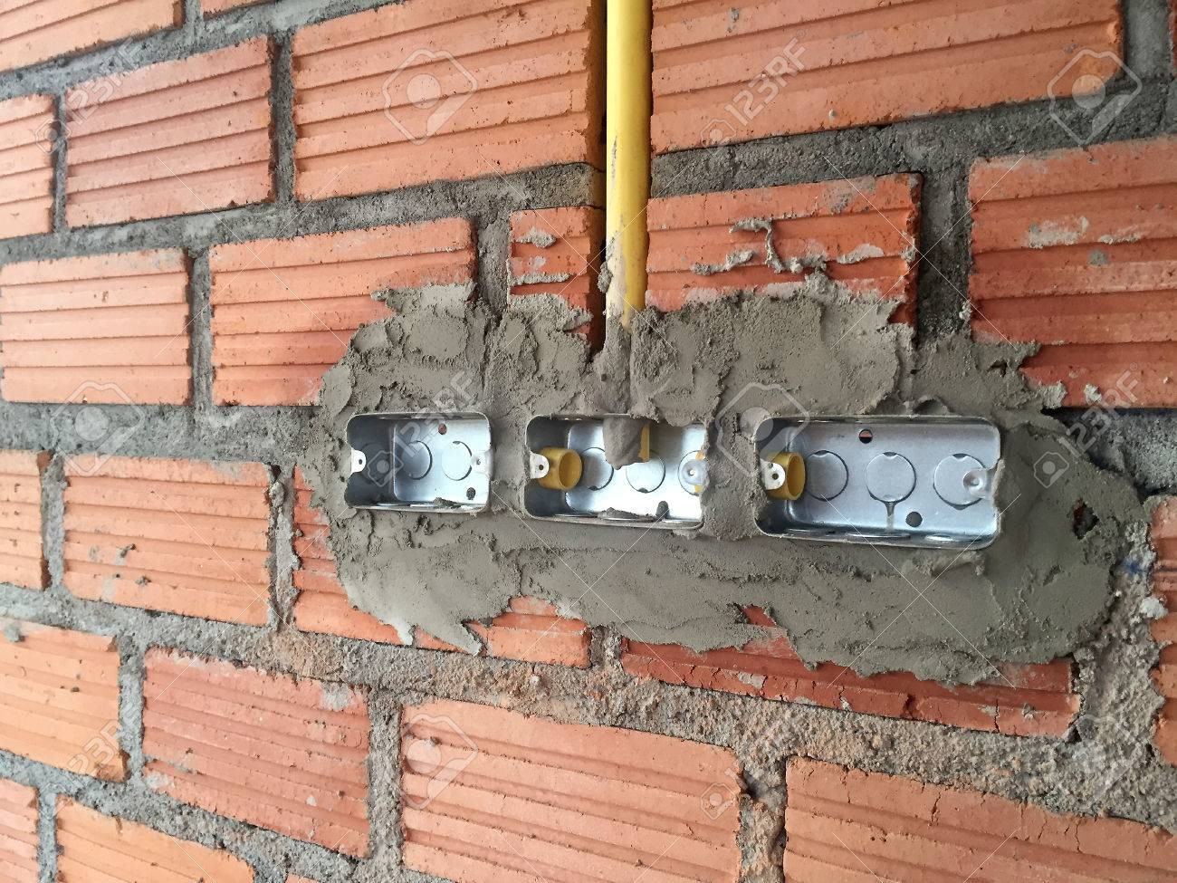 electric sockets installation in brick walls at house construction rh 123rf com House Electrical Wiring Basics Electrical Outlet Wiring Diagram