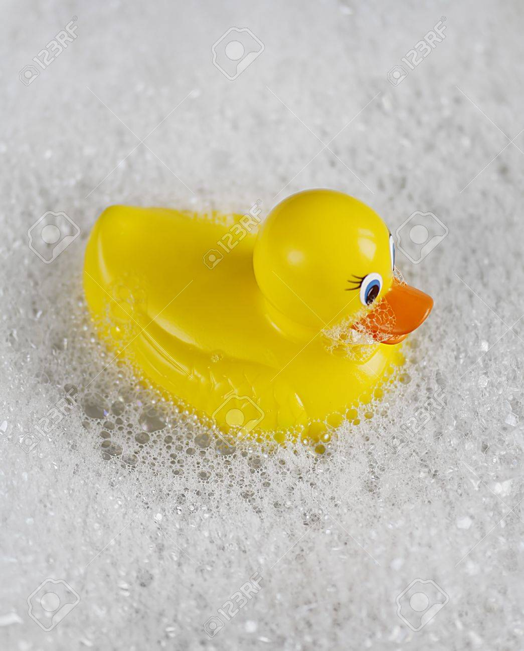 Bathtime fun with a yellow rubber ducky in a bathtub full of water and bubbles. Stock Photo - 9450308