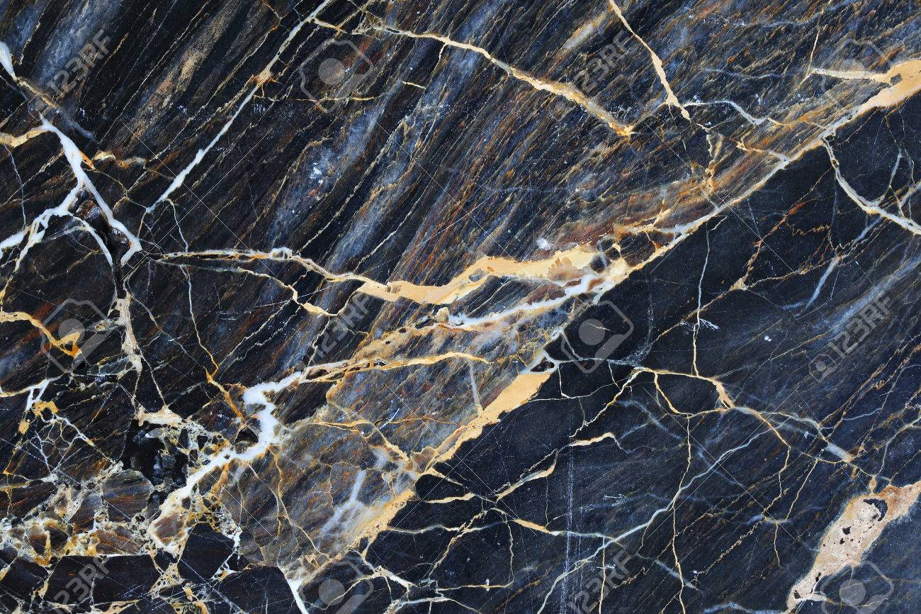 gold and cream color patterned natural of dark blue gray marble