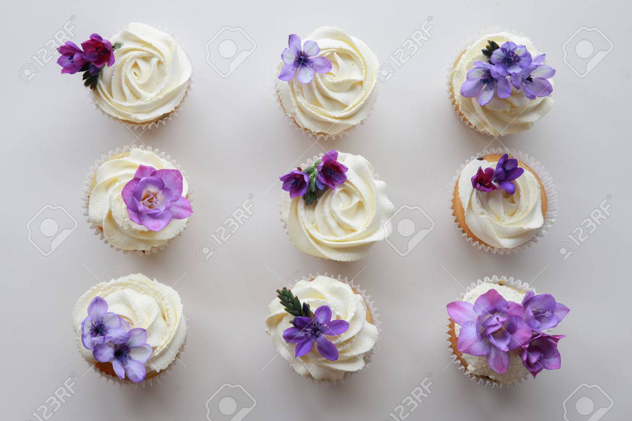 homemade purple freesia flowers on vanilla cupcakes with whipped