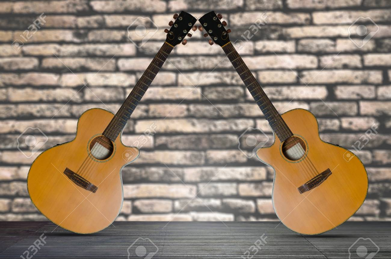 two acoustic guitar on the wooden floor against brick wall background. - 94735468