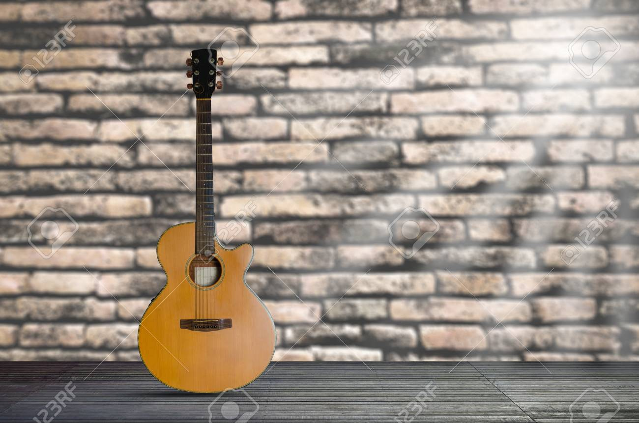 acoustic guitar on the wooden floor against brick wall background. - 95081015