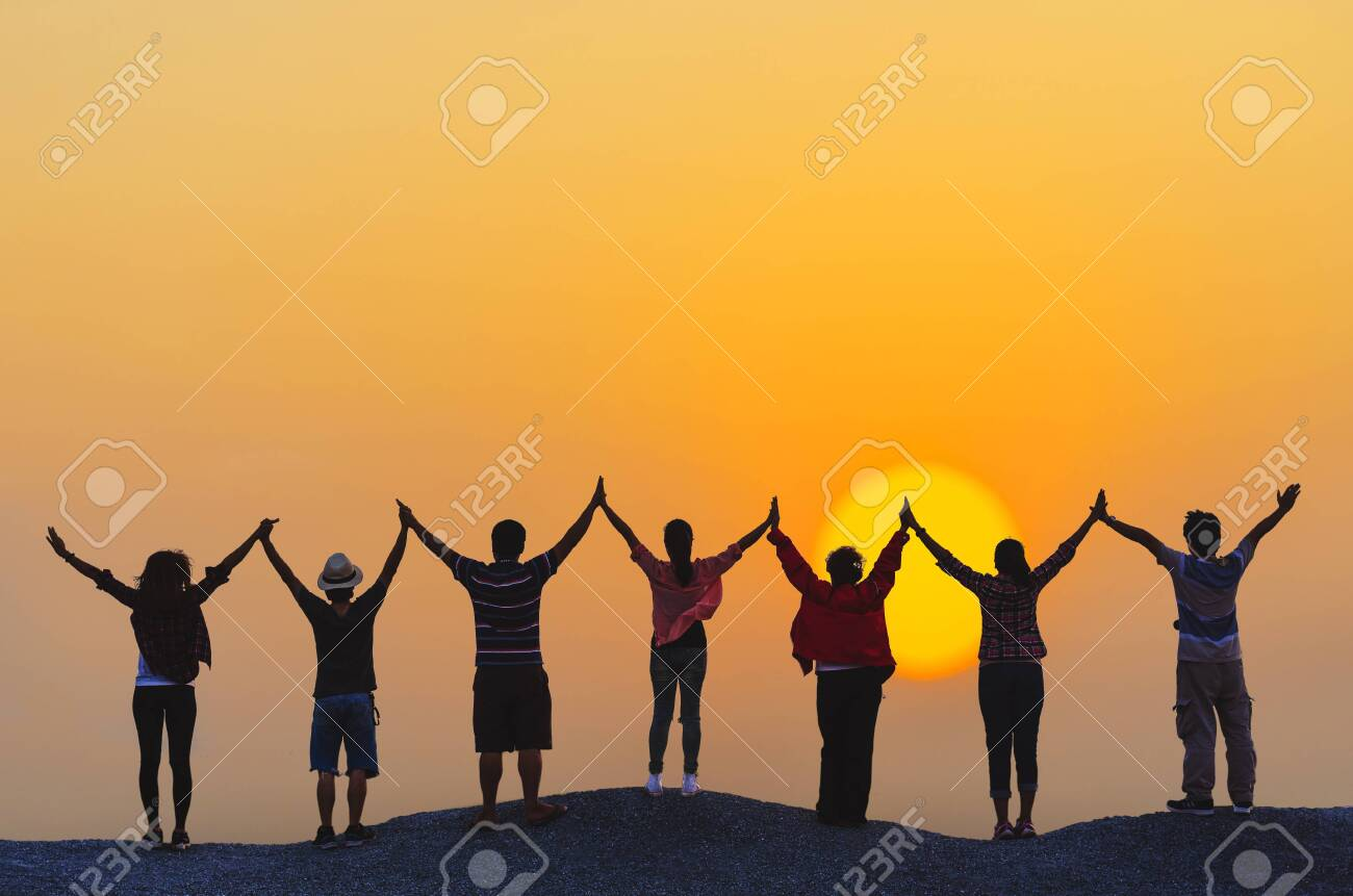 teamwork concept silhouette diversity people show hands high up over head successful partner together at sunset on top rock hill. - 128100265