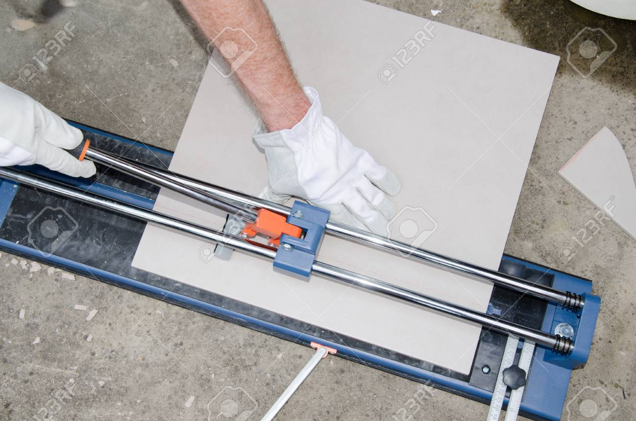 Laying Floor Tiles, Tiler Using A Tile Cutter Stock Photo, Picture ...