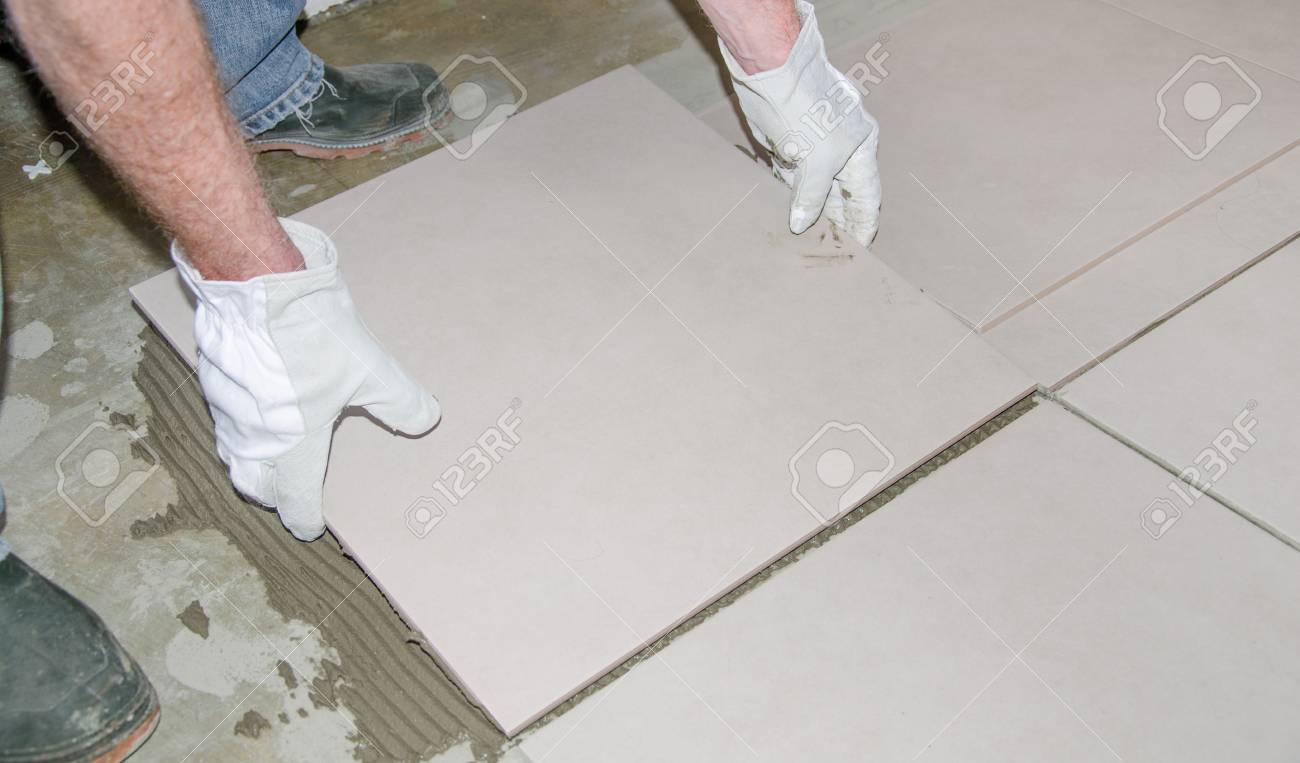 Laying Tiles Tiler Laying A New Tile On The Floor Stock Photo