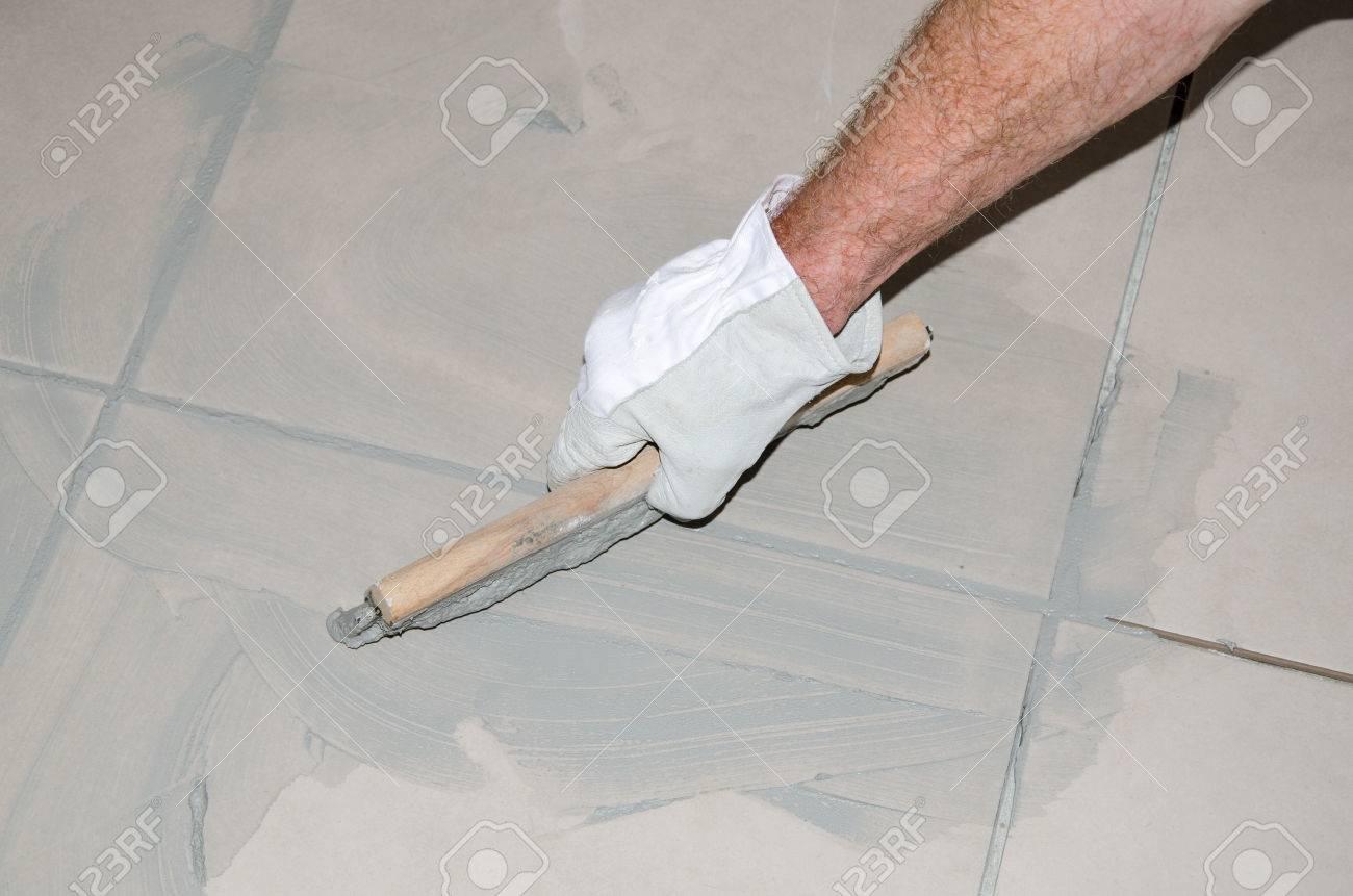 Laying Floor Tiles, Tiler Filling Up Joints Between Ceramic Tiles ...