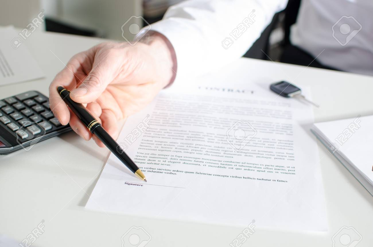 car salesman showing a sales contract at office stock photo picture