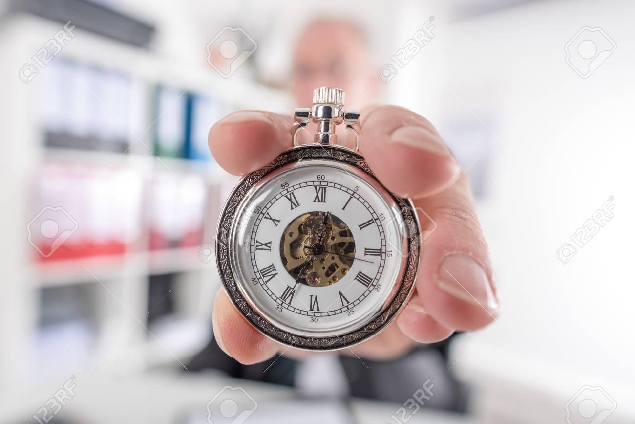 El hombre de negocios que sostiene un reloj de bolsillo Foto de archivo -  47536467