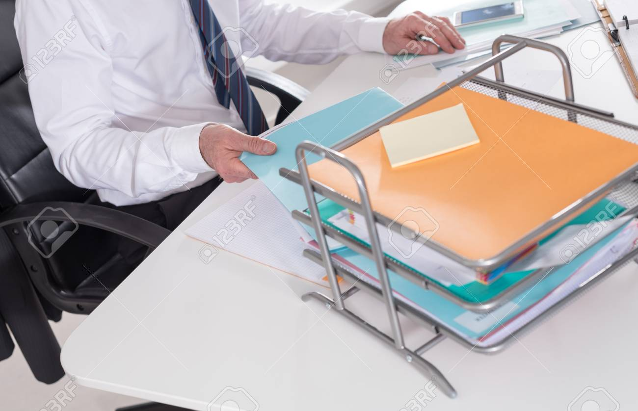 Businessman taking a record of his paper tray at office