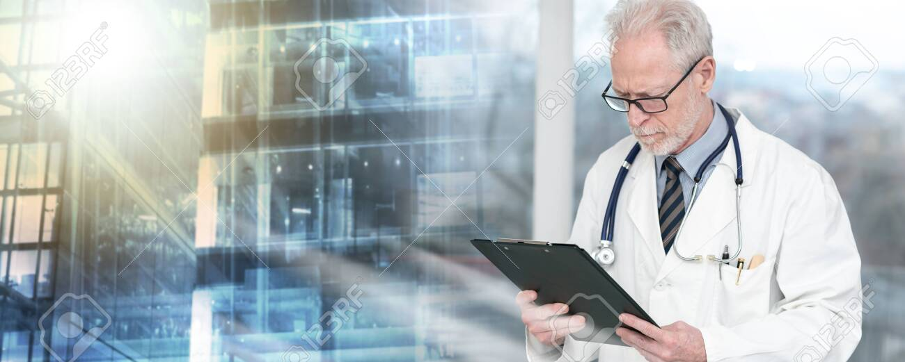 Senior doctor standing and reading notes on clipboard; multiple exposure - 143126007