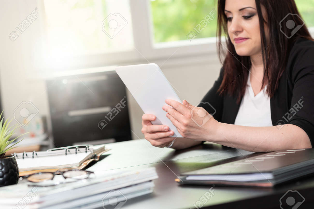 Businesswoman using digital tablet at workplace - 154443747