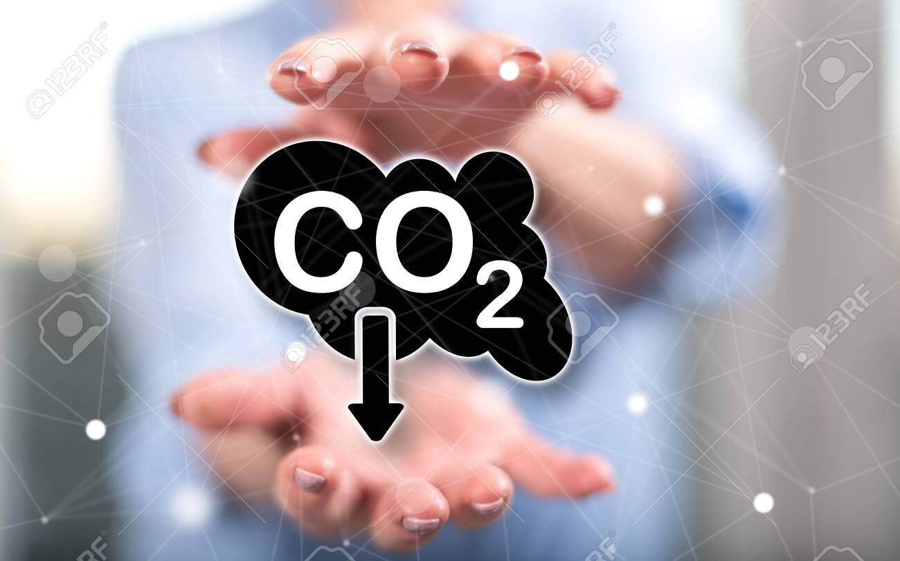 Carbon reduction concept between hands of a woman in background - 155640295