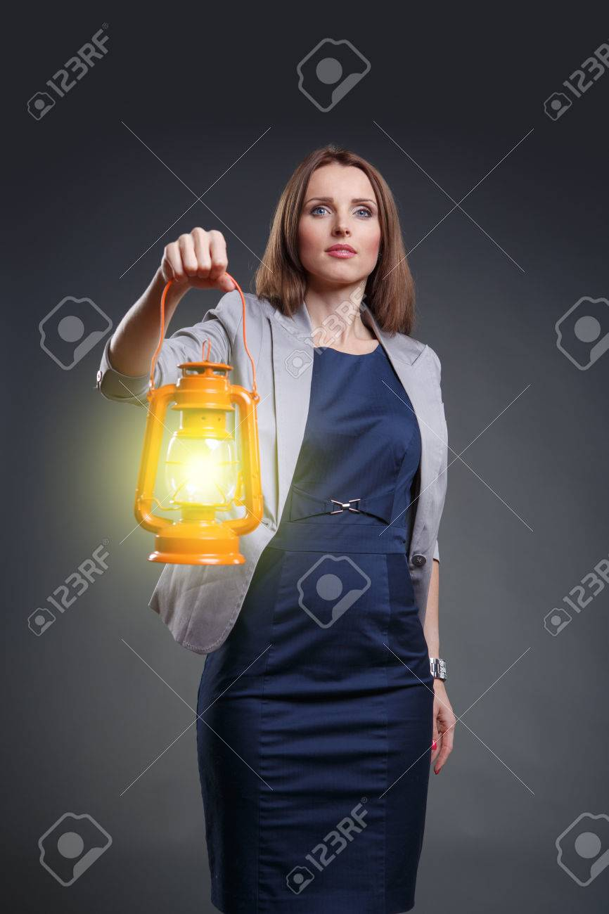 Studio portrait of a courageous and decided woman with the lantern - 24041958