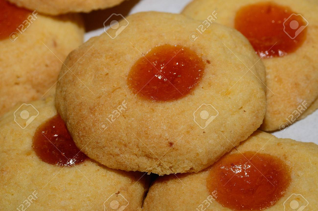 Many Of The Same Christmas Cookies With Apricot Jam In The Middle