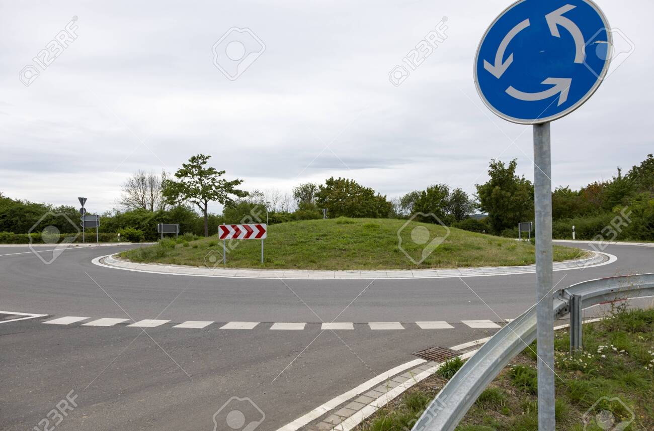 roundabout without cars with a sign that indicates it, cloudy day - 155957699