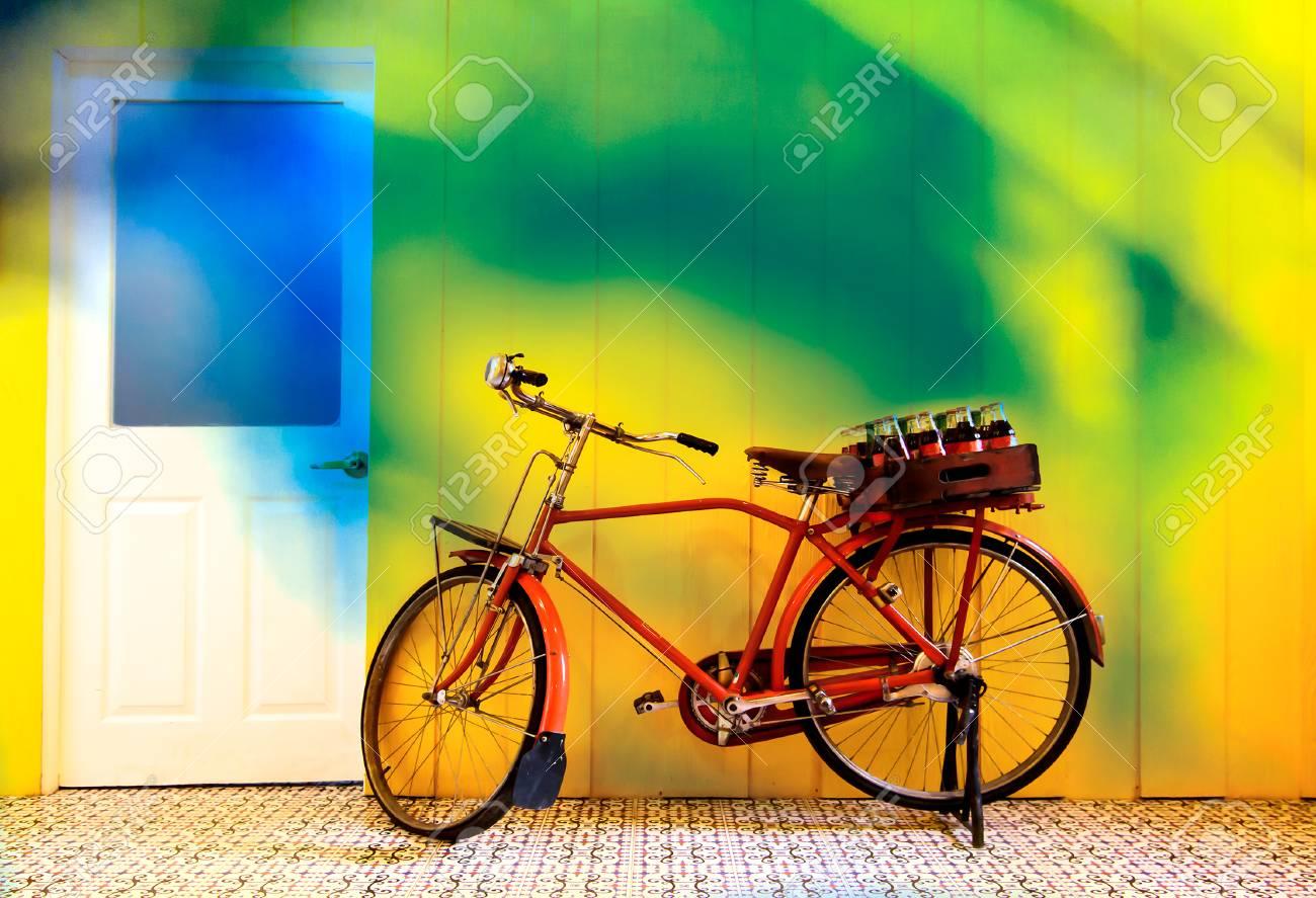 Bicicletta Antica E Di Bottiglie Di Bibite In Scatola La Priorità Bassa è La Parete Variopinta E La Porta Bianca
