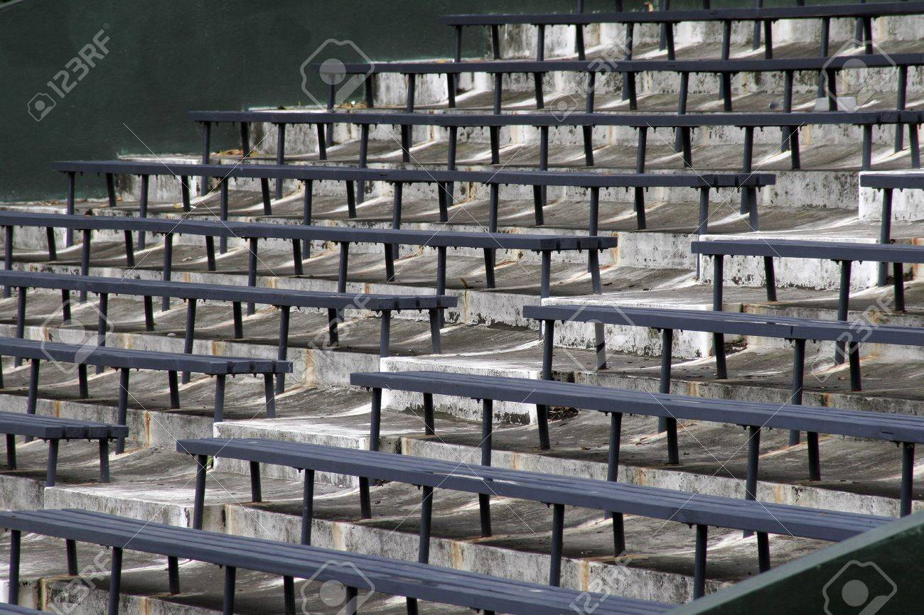 blue benches on a grey concrete ground in rows, stadium seats