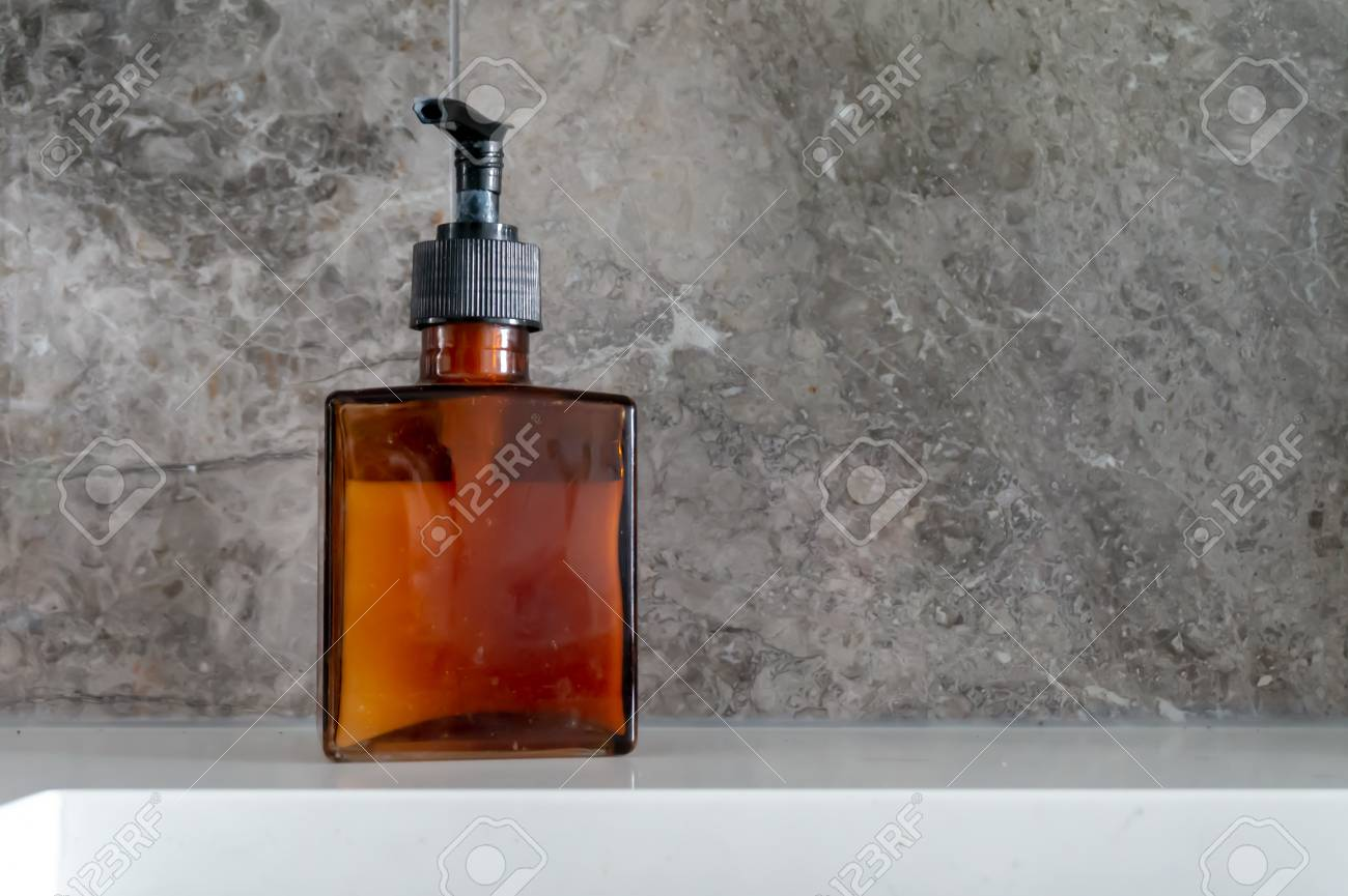 Hand soap dispenser in a brown glass, square bottle, with black..