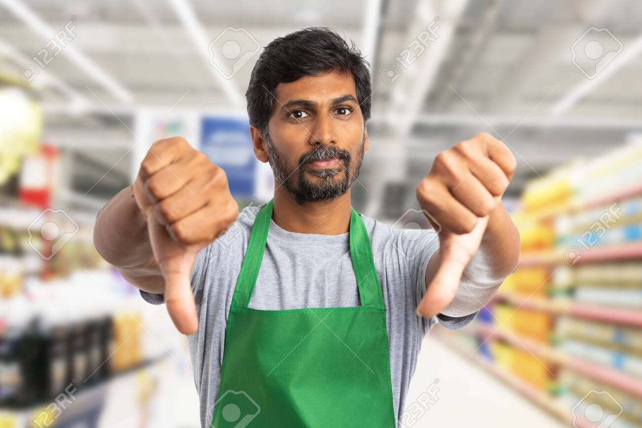 Indian supermarket or hypermarket employee man making double thumbs-down gesture as dislike concept - 118780803