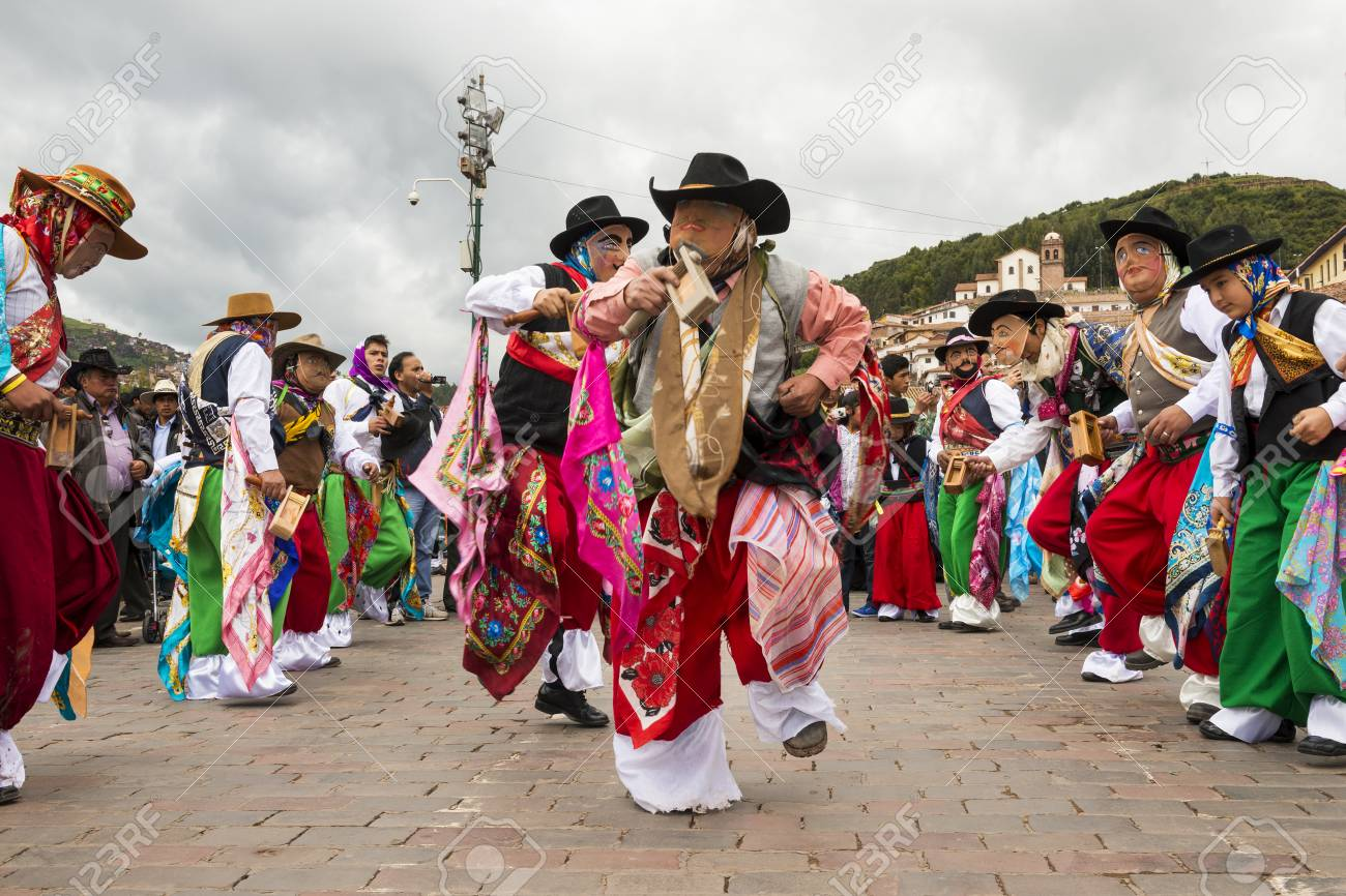 Cuzco, Peru - December 25, 2013: Man waering traditional clothes and masks dancing the Huaylia in the Christmas day in front of the Cuzco Cathedral in Cuzco, Peru. - 74196571