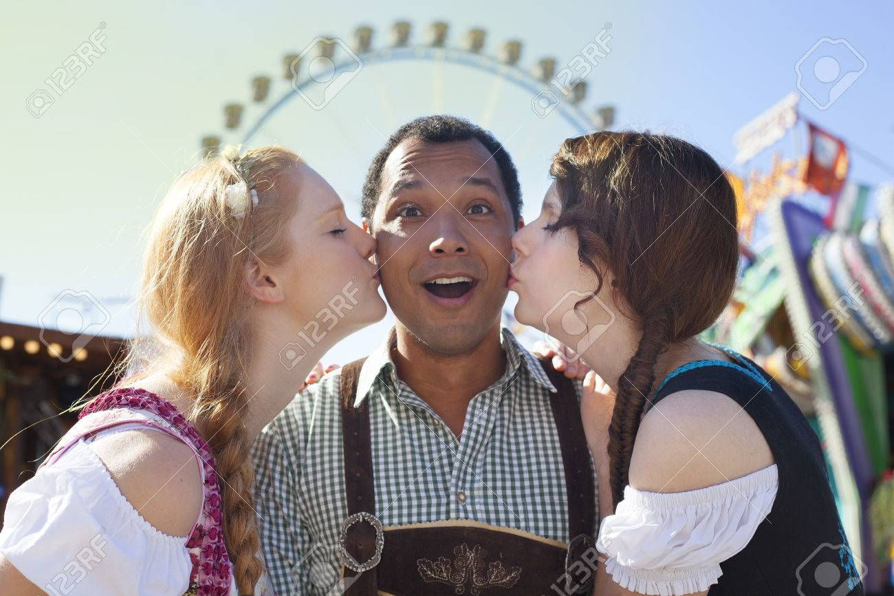 Young man getting kissed on the cheek by two german girls at young man getting kissed on the cheek by two german girls at oktoberfest stock photo voltagebd Image collections