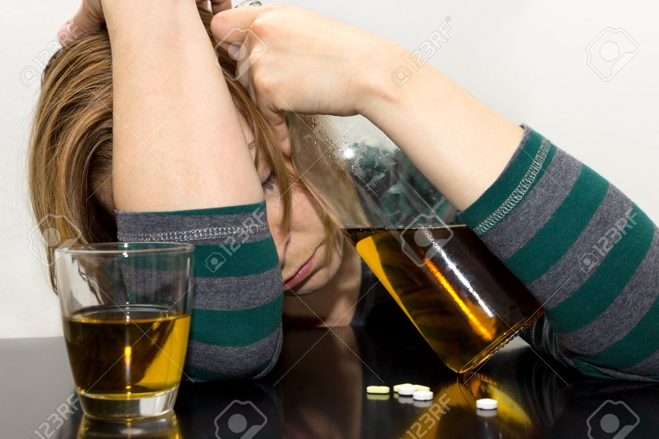 Drunk woman with bottle in her hand and pills on the table - 25905007