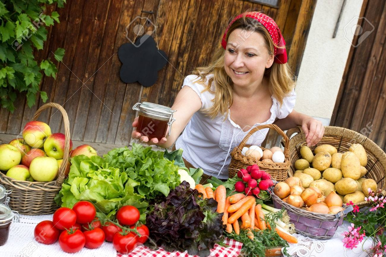 A cute marketwoman offers honey at the market - 61705999