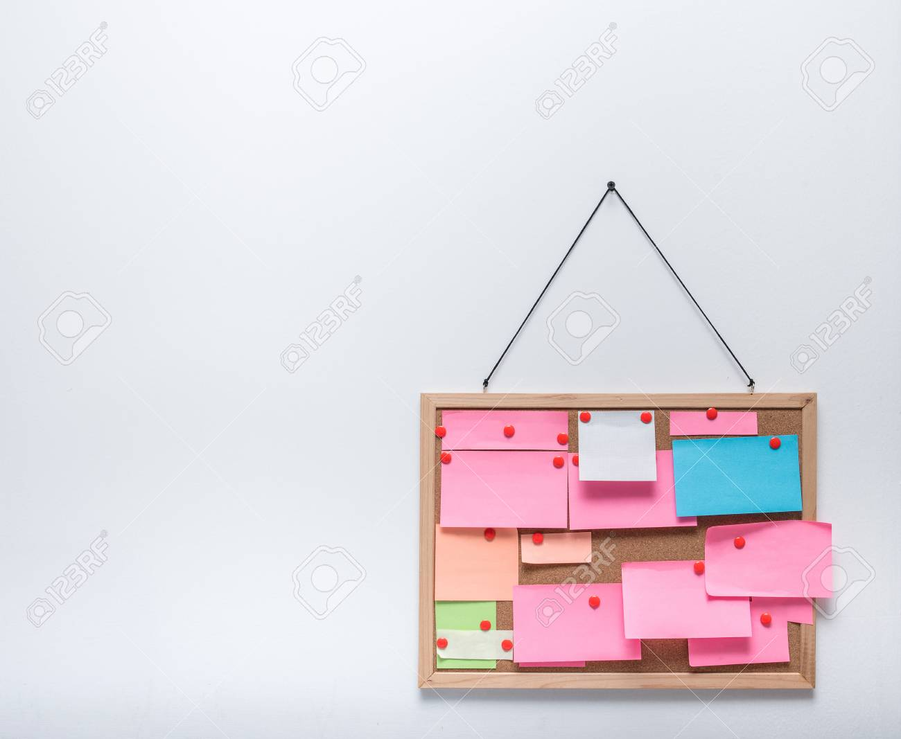 Sticky Notes On Hanging Cork Bulletin Board On White Wall Background