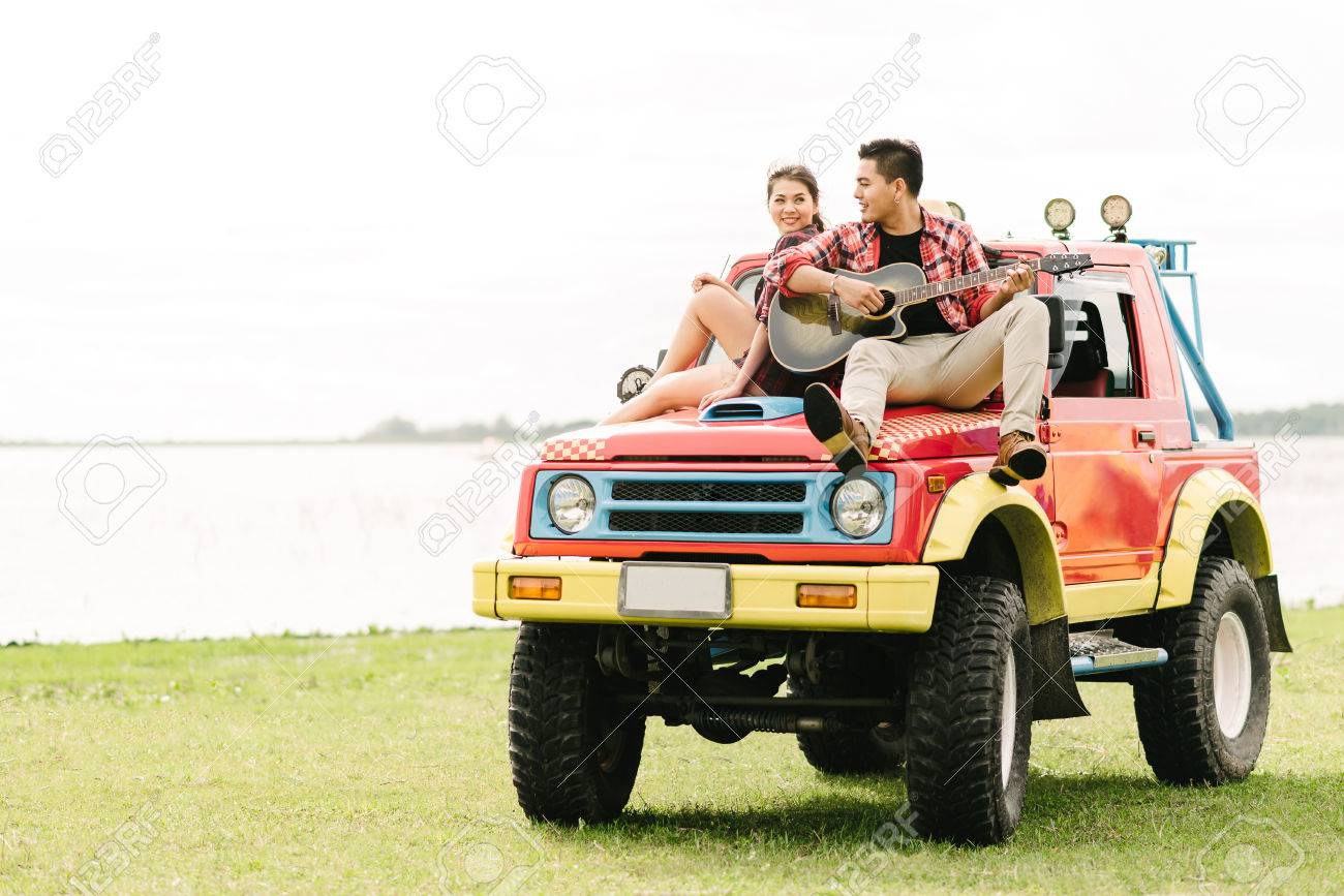 Happy Asian young couple in love playing guitar while sitting on a car  during vacation Stock