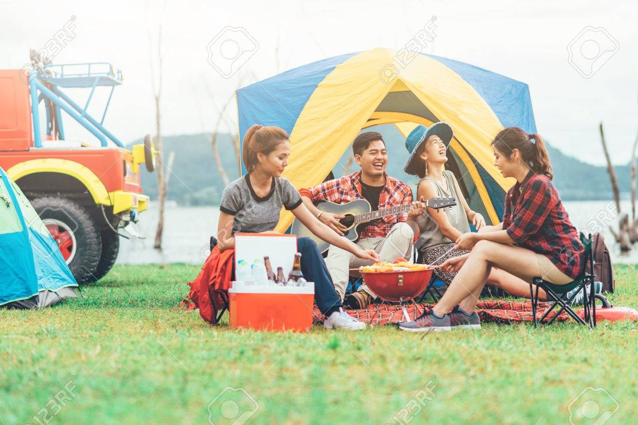 Group of Asian friends having fun eating barbecue outdoor while camping and play guitar. - 83853138