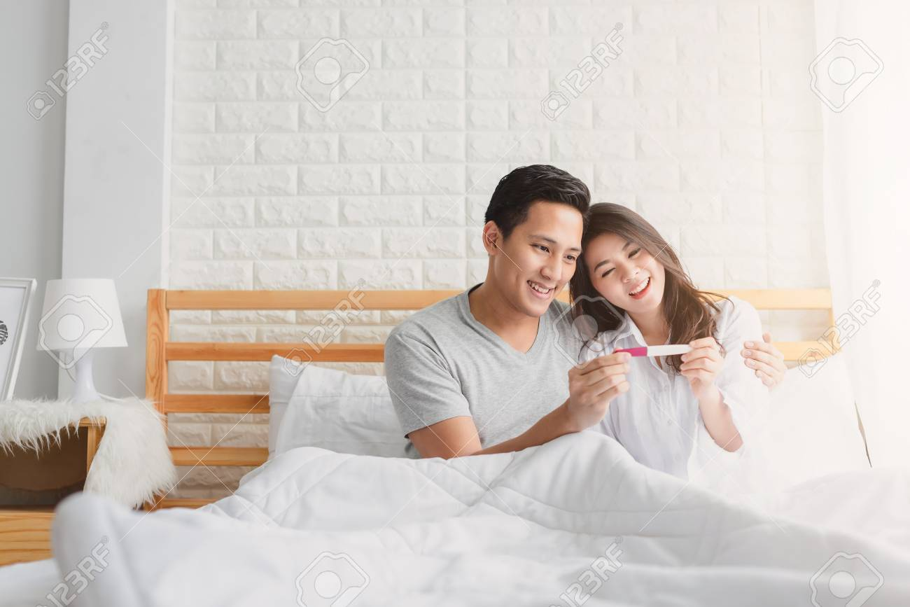 Happy Asian couple smiling after find out positive pregnancy test in bedroom at home - 89203934