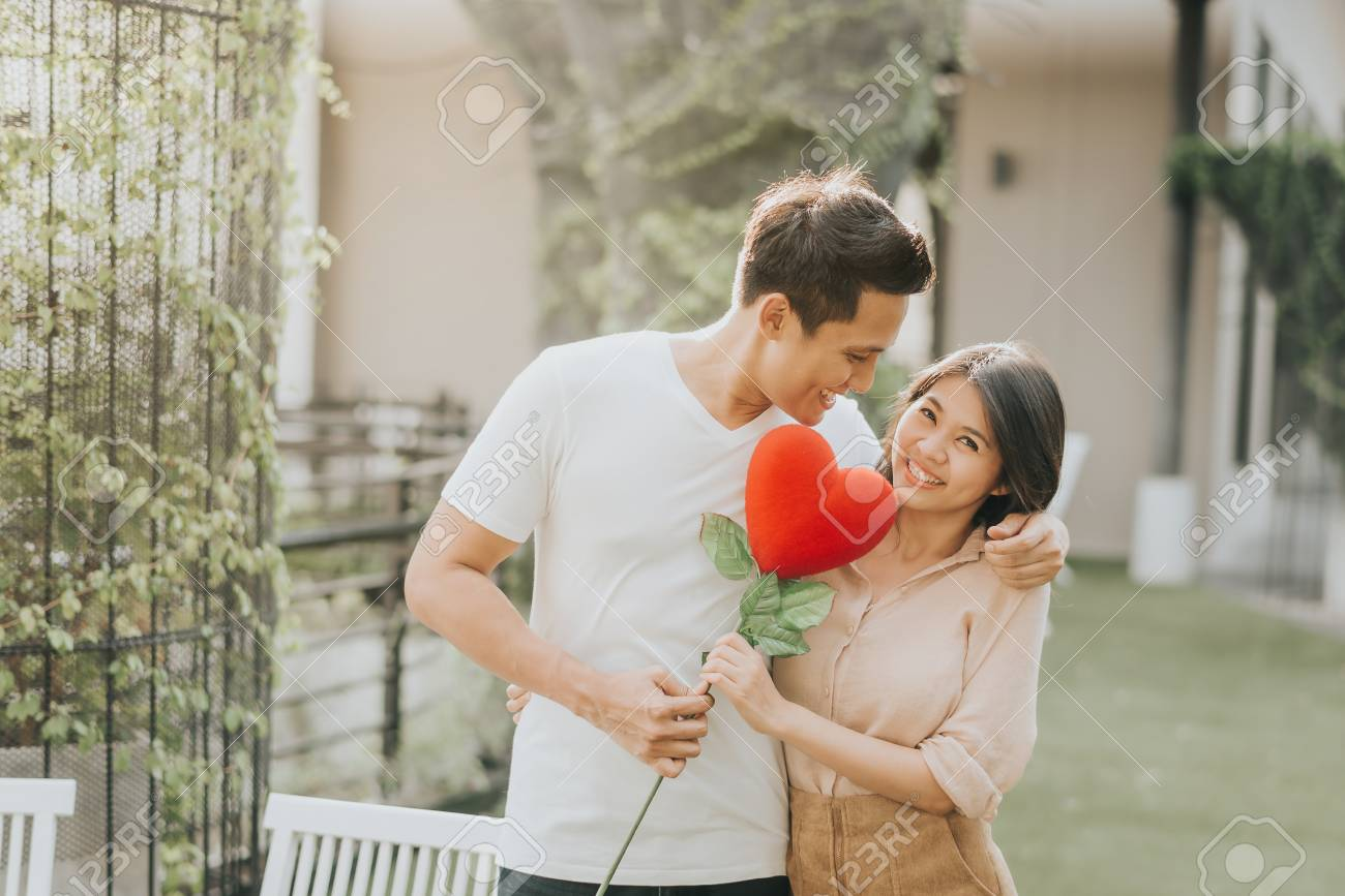 Romantic happy Asian couple in love having fun with heart flower while hugging. Vanlentine day concept. - 92981103