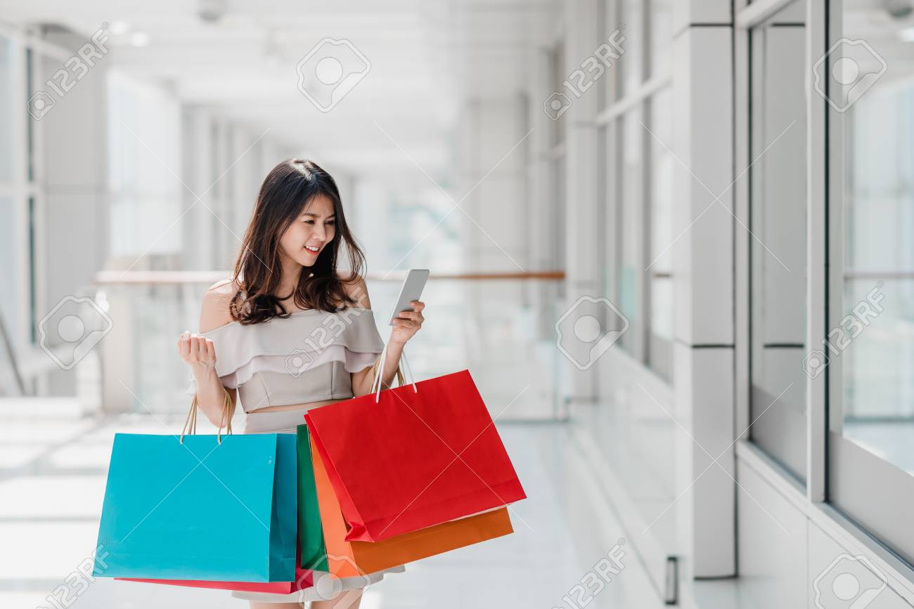 Beautiful young happy Asian woman with colorful shopping bag using smartphone while shopping in mall - 94020636
