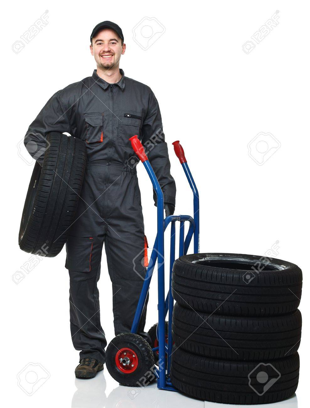 man with garage suit and tires on white background Stock Photo - 8815369