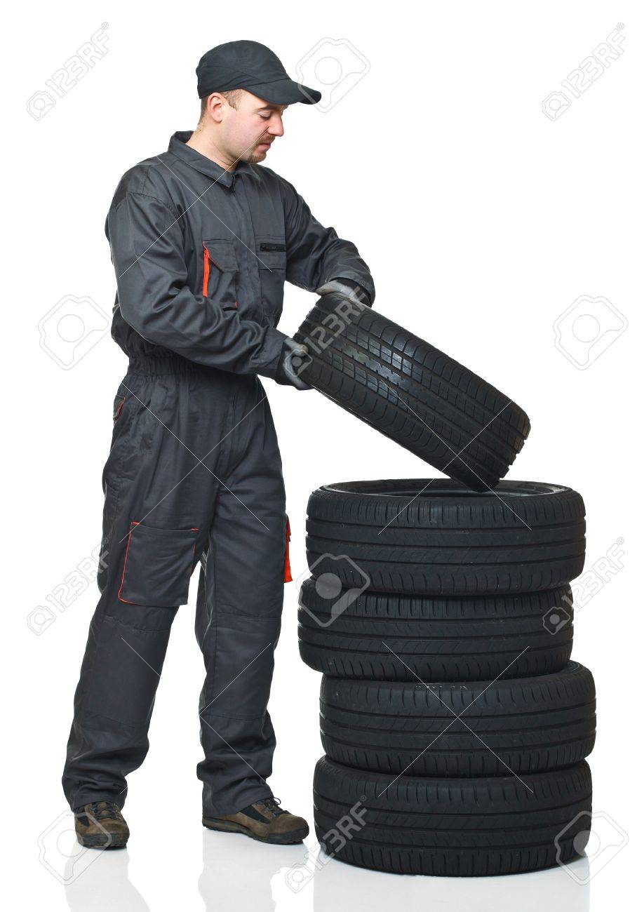 young mechanic move tires isolated on white background Stock Photo - 8815404