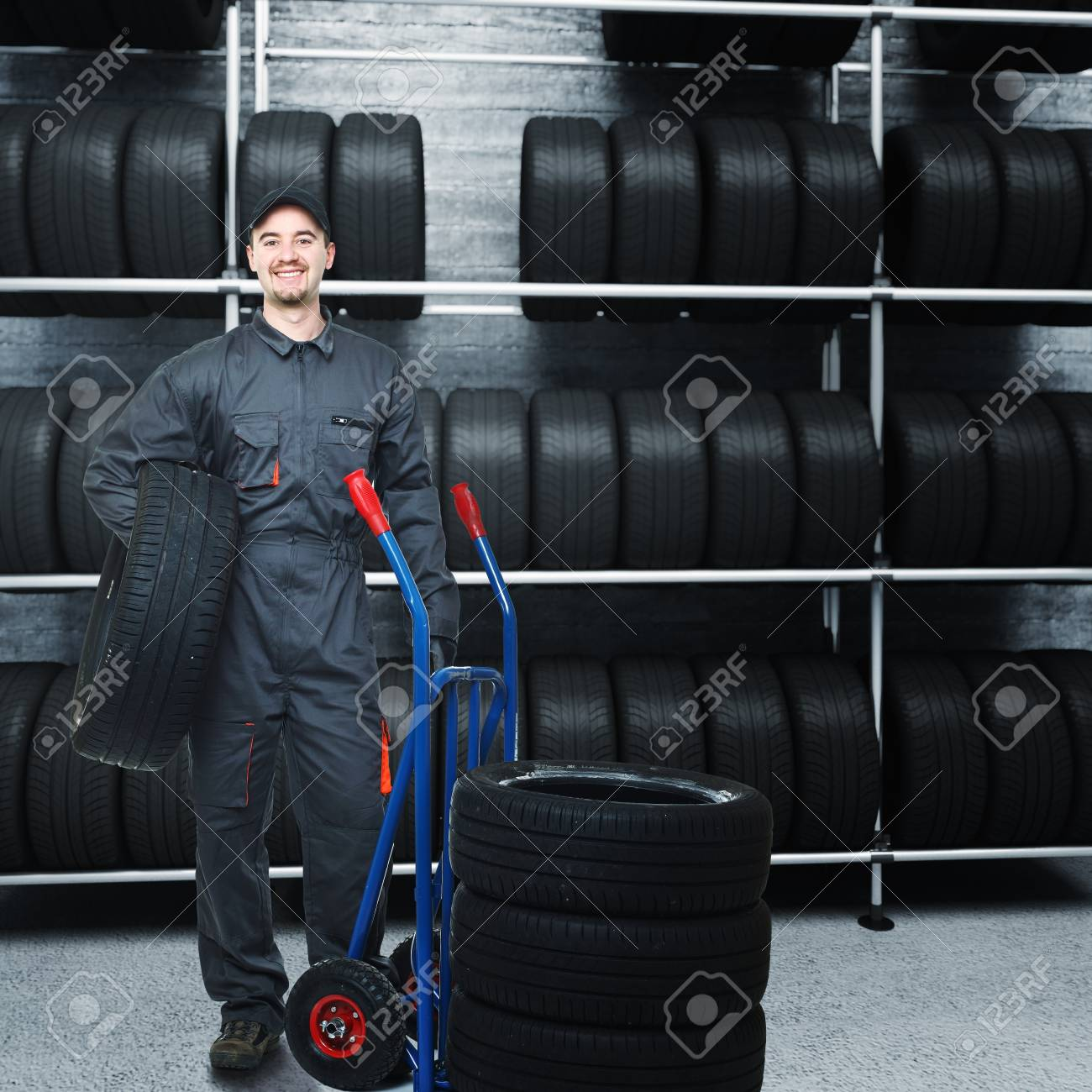 caucasian mechanic at work with tires and 3d garage background Stock Photo - 8943882