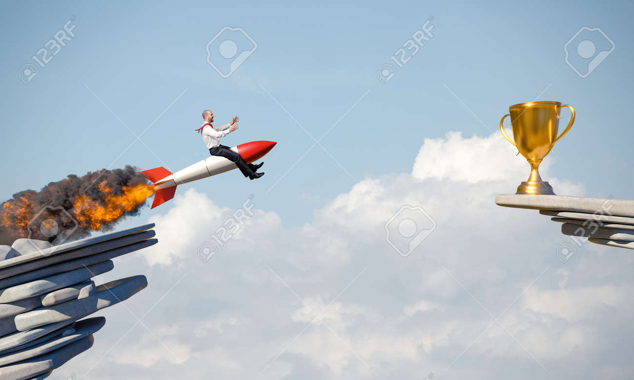 businessman uses a rocket to reach an award. concept of determination. - 172162160