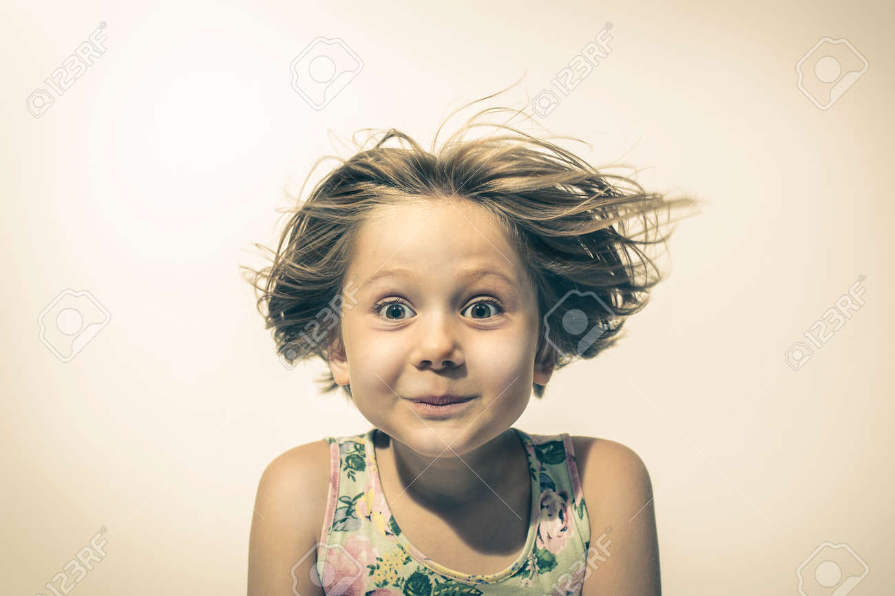 little girl looks in camera with funny and amused expression. studio portrait - 173236172